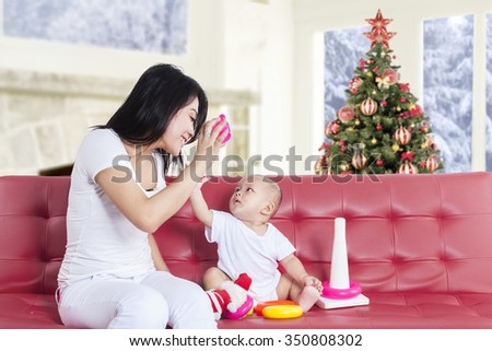 Picture of happy young mother and her baby playing on the sofa with christmas tree decoration at home