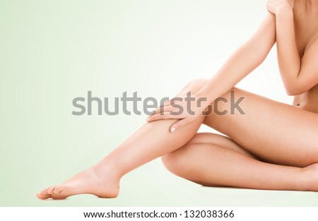 picture of healthy naked woman legs over green background - stock photo