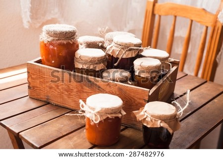 Picture of home made jam  in jars. Homemade preserves (conserve) concept in country kitchen. Rustic style. - stock photo