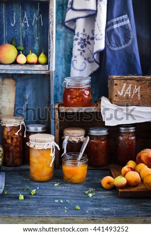 Picture of home made jam in jars. Homemade preserves (conserve) concept in country kitchen. Rustic style - stock photo