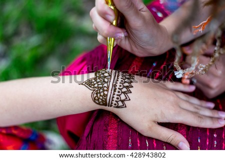 Picture of human hand being decorated with henna Tattoo. mehndi hand
