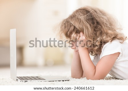 Picture of lovely little girl using laptop in home - stock photo