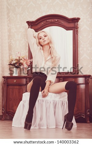 picture of lovely young woman in sexy outfit sitting on a ottoman against mirror - stock photo