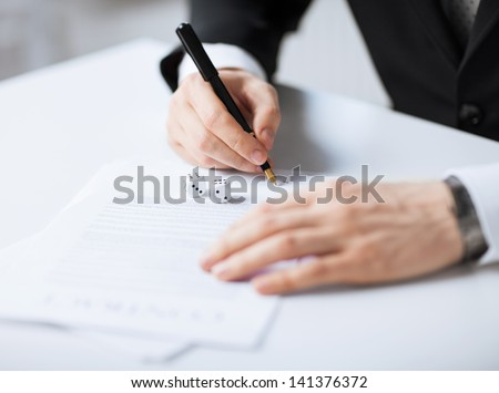 picture of man hands with gambling dices signing contract - stock photo