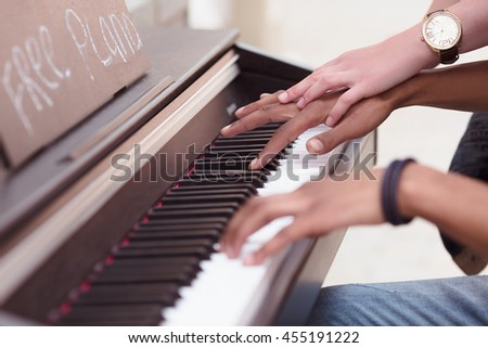Picture of man playing piano while lady explaining him something. Professional musician playing outdoors. Closeup of keyboard of piano. - stock photo