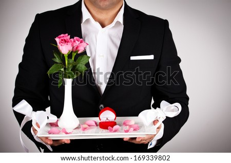 Picture of man with rose and wedding ring. Concept of honeymoon, wedding, valentine day. - stock photo