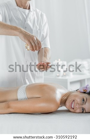 Picture of masseur doing healing olive oil body massage - stock photo