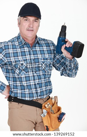 picture of mature carpenter holding drill - stock photo
