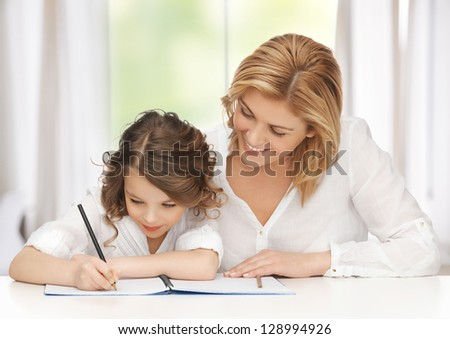 picture of mother and daughter doing home work - stock photo
