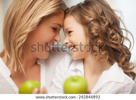 picture of mother and daughter with green apples - stock photo