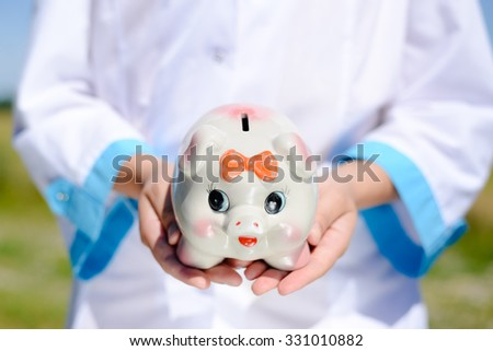 Picture of nurse's hands holding piggy bank. Closeup of ceramic moneybox on blurred outdoor background. - stock photo