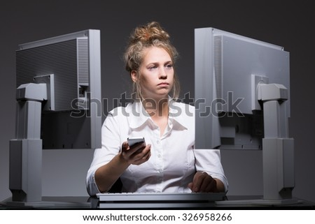 Picture of overworked woman with mobilephone sitting at computers