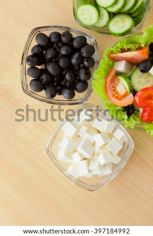 Picture of plates with vegetables and greek salad on table - stock photo
