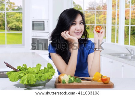 Picture of pretty Asian woman preparing vegetable salad and holding a tomato while smiling at the camera in the kitchen - stock photo