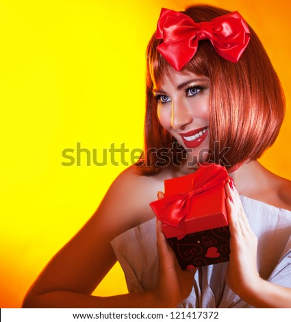 Picture of pretty woman with red bow in hair holding gift box in hands, gorgeous female with red hair isolated on yellow background, attractive girl wearing stylish festive dress, New Year party - stock photo