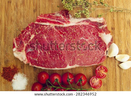 Picture of raw beef steak on a dark wooden table with tomato,oregano and onion garlic - stock photo