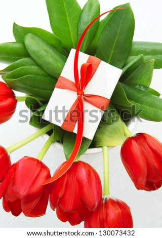 Picture of red fresh tulip flowers with luxury present for mom, beautiful floral bouquet with little giftbox on the top isolated on white background, happy mothers day, romantic still life - stock photo