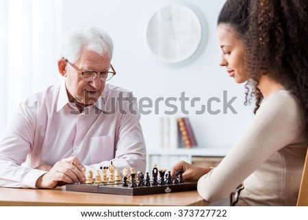 Picture of retired man playing chess with private carer - stock photo