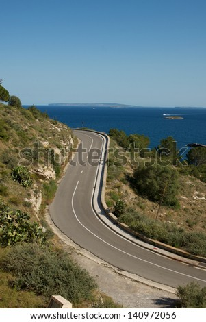 Picture of road turns, with a beautiful sea view and islands in the background - stock photo