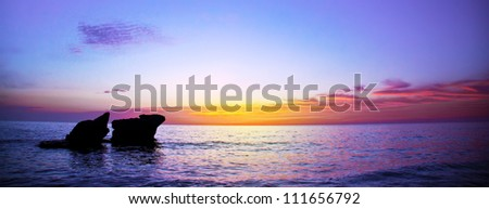 Picture of romantic purple sunset over seascape, peaceful ocean landscape, beautiful rocks in evening sea, calm autumn weather, violet dusk on coastline, night scenery of Mediterranean sea, travel - stock photo