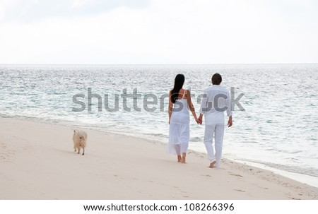 Picture of romantic young couple having a walking on the sea shore with dog - stock photo