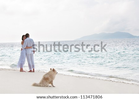 Picture of romantic young couple on the sea shore with dog - stock photo