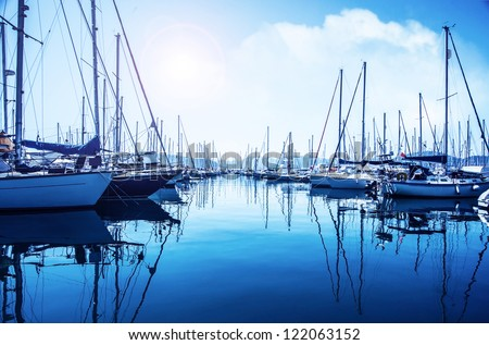 Picture of row of luxury sailboats reflected in water, yacht port on the bay, water transport, ocean transportation, beautiful vessel in the harbor, summer vacation, active lifestyle, holiday concept - stock photo