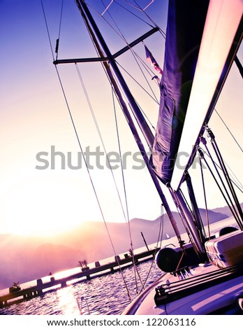 Picture of sailboat on purple sunset, luxury yacht in the sea, romantic vacation and travel, bright light in the sky, peaceful beach view, water sport, freedom and adventure concept - stock photo