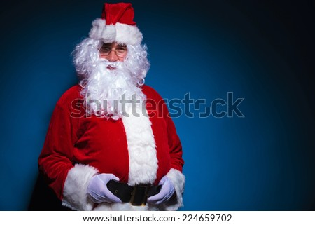 Picture of Santa Claus looking at the camera while holding his black belt. - stock photo