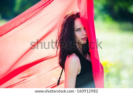 Picture of sexy yang dark haired women with red fabric.