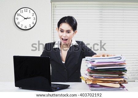 Picture of shocked businesswoman looking at the laptop screen with a pile of paperwork on the table - stock photo