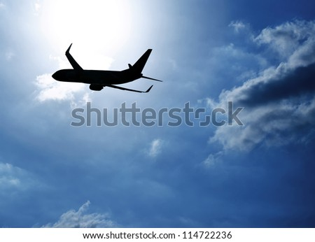 Picture of silhouette airplane in blue sky, journey trip, airliner in heaven, plane over clouds background, air transportation, luxury airline, business destination, fast flight, tourism concept - stock photo