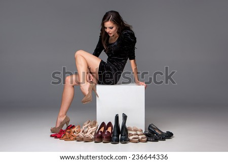 picture of sitting young attractive girl trying on high heeled shoes on a gray background - stock photo