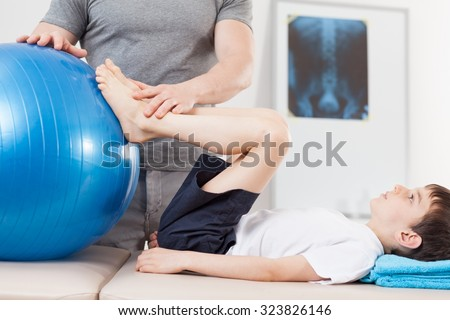 Picture of small patient doing exercises with fitness ball - stock photo