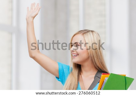 picture of smiling student with folders waving her hand - stock photo