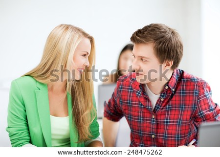 picture of smiling students looking at each other at school - stock photo