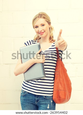 picture of smiling teenage girl with laptop showing thumbs up - stock photo