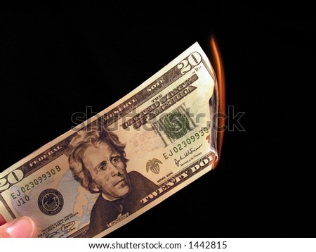 Picture of someone burning a 20 dollar bill. - stock photo
