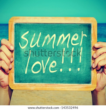 picture of someone on the beach holding a blackboard with the sentence summer love written on it, with a retro effect - stock photo