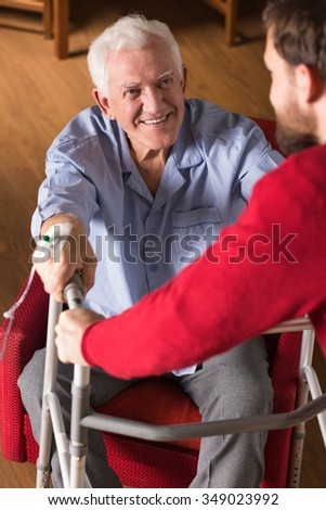 Picture of son helping old disabled father - stock photo
