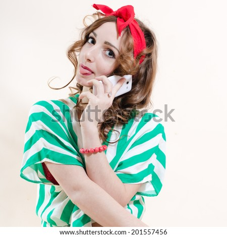 picture of speaking on mobile cell phone showing tongue funny sexy pinup girl blond young beautiful woman having fun posing studio shot over white wall copy space background portrait