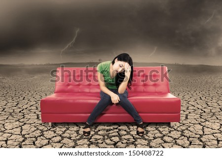 Picture of stress woman sitting on red sofa with cracking soil and bad weather - stock photo