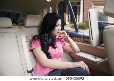 Picture of successful young businesswoman sitting on the seat back of a luxury car - stock photo