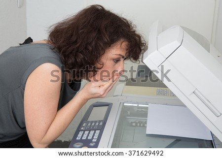 Picture of surprised business woman with smoking copier - stock photo