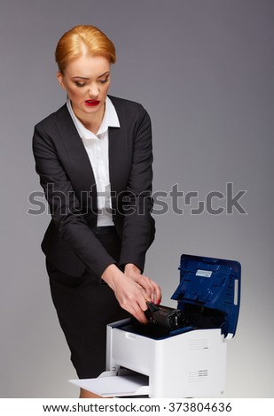 Picture of surprised businesswoman with broken printer - stock photo