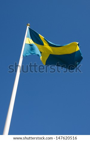 Picture of Swedish flag waving in the wind, on a blue sky - stock photo
