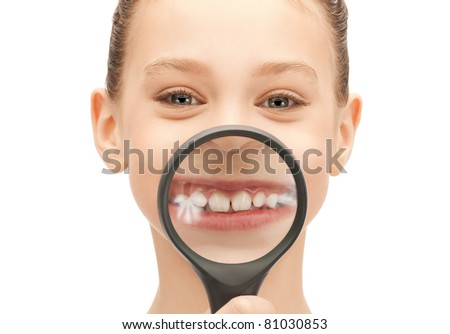 picture of teenage girl with magnifying glass showing teeth - stock photo