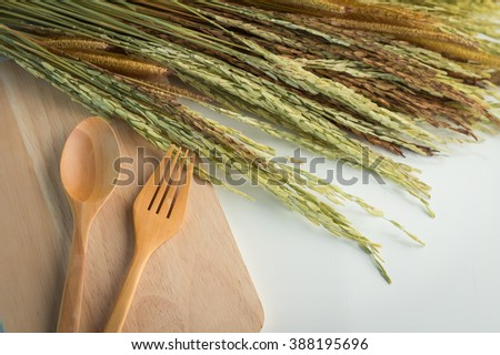 picture of the fork and spoon with the ears of wheat on the old wood board at white table