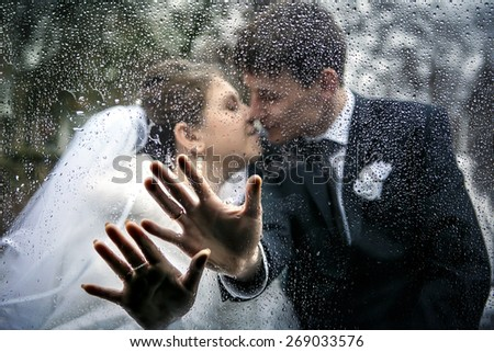 picture of the hands of a bride and a groom on the car window with drops from a rain on the background a kiss of the groom and the bride - stock photo