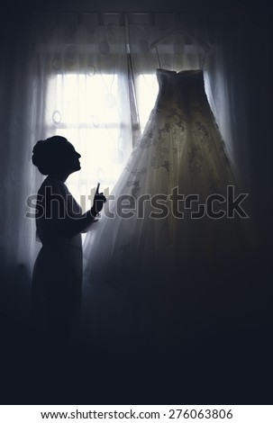 Picture of the silhouette of a woman with her wedding dress.